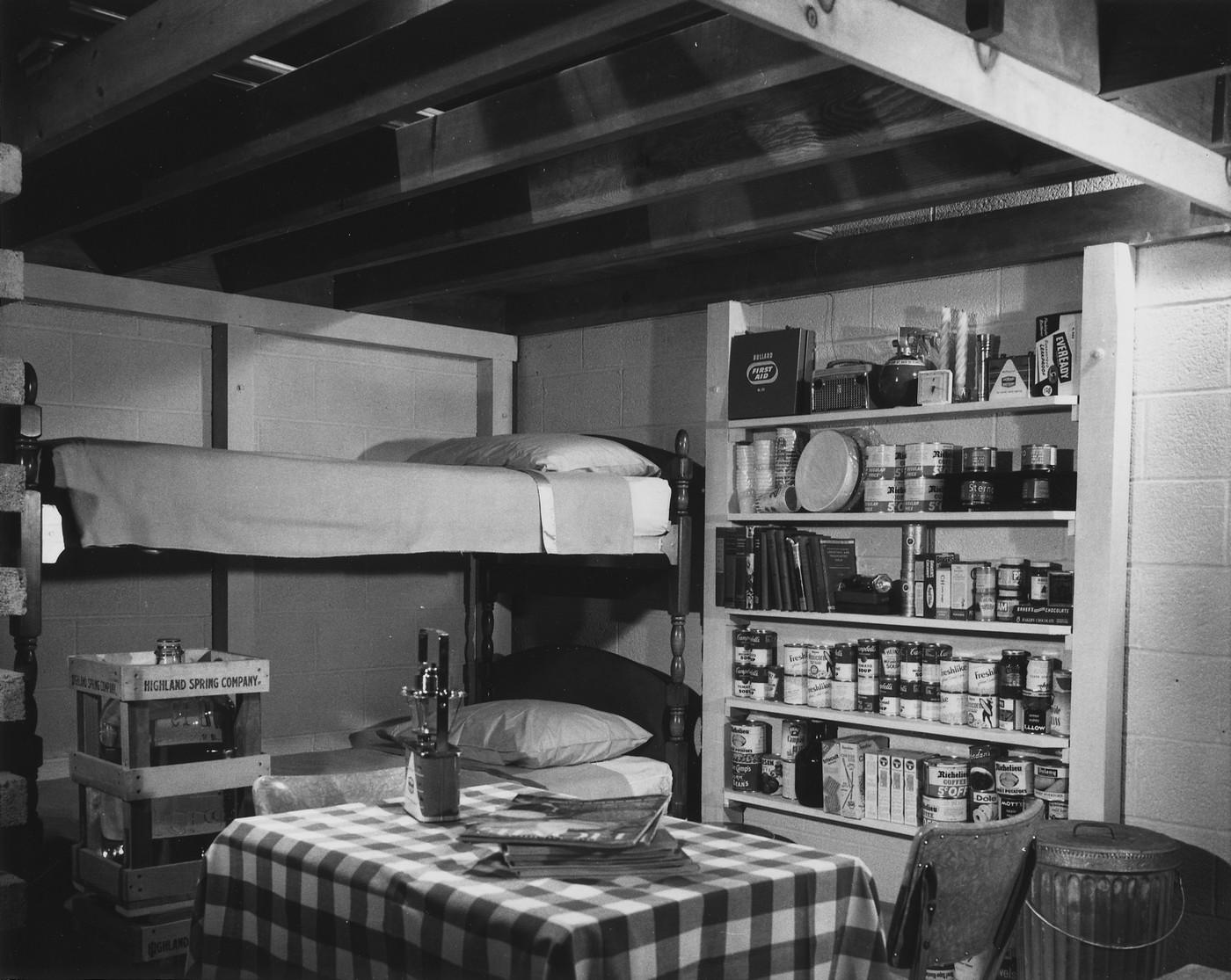 Интерьер семейного ядерного бомбоубежища, устроенного в подвале дома. В убежище имеется 14-дневный запас продовольствия и воды, радио с батарейным питанием, автономные источники света, набор медикаментов и инструментов. Ориентировочно 1957 год