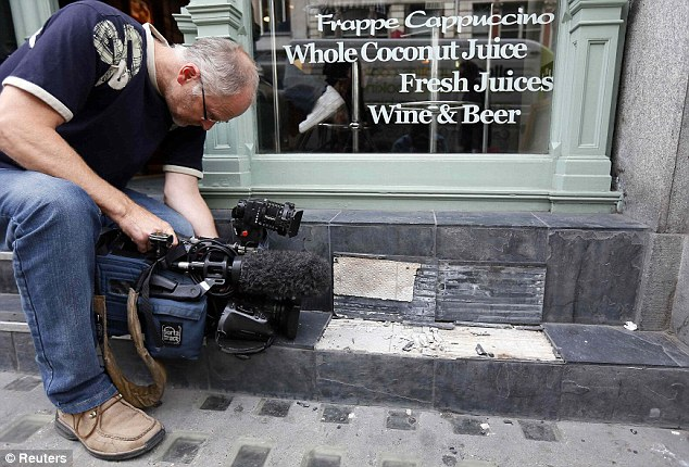 Оператор снимает плитку, отвалившуся у здания кафе под воздействием солнечного света