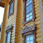 Деревянный дом из цельного бруса, выдержанный в стилистике русского терема с использованием резных декоративных элементов (наличники, окантовка крыши, розетки и др.)